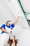 Worker spraying ceiling with spray bottle Royalty Free Stock Image