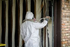 Worker spraying closed cell spray foam insulation on a home wall Royalty Free Stock Photo
