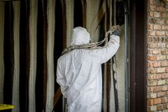 Worker spraying closed cell spray foam insulation on a home wall Stock Photography
