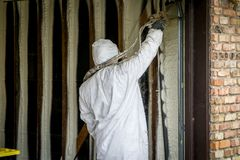 Worker spraying closed cell spray foam insulation on a home wall Royalty Free Stock Photography
