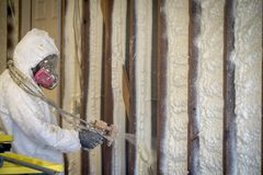 Worker spraying closed cell spray foam insulation on a home wall Royalty Free Stock Image