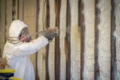 Worker spraying closed cell spray foam insulation on a home wall. Worker spraying closed cell spray foam insulation on a home that was flooded by Hurricane stock images