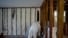 Worker spraying closed cell spray foam insulation on a home wall. Worker spraying closed cell spray foam insulation on a home that was flooded by Hurricane stock video