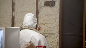 Worker spraying closed cell spray foam insulation on a home wall
