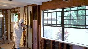 Worker spraying closed cell spray foam insulation on a home wall. Worker spraying closed cell spray foam insulation on a home that was flooded by Hurricane stock footage