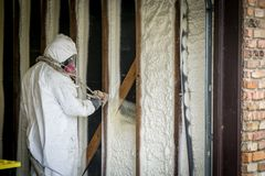 Worker spraying closed cell spray foam insulation on a home wall Stock Photos