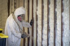 Worker spraying closed cell spray foam insulation on a home wall Royalty Free Stock Photos