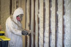 Worker spraying closed cell spray foam insulation on a home wall Stock Images