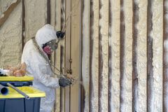 Worker spraying closed cell spray foam insulation on a home Royalty Free Stock Images