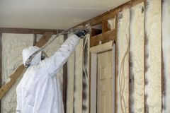Worker spraying closed cell spray foam insulation on a home Stock Photo