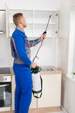Worker Spraying Insecticide On Shelf Royalty Free Stock Photo