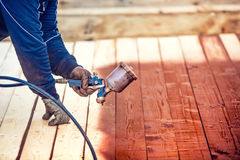 Worker spraying paint over timber wood. Construction worker with spray gun Stock Photos
