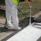 Crosswalk repairing and painting. Worker spraying pedestrian crosswalk at a street,  repairing and painting Stock Images