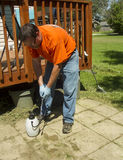 Worker Spraying Weed Killer On A Customers Patio Royalty Free Stock Photos