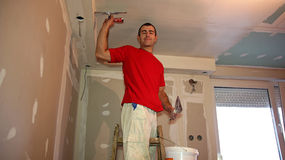 Worker Spreading Plaster with Trowel to Gypsum Board royalty free stock image