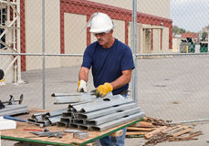 Worker Stacking Metal Studs. Construction worker stacking metal studs to be sawed stock photos