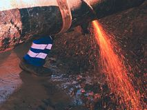 Worker staff cut big metal tube with grinder. Burning red parks Royalty Free Stock Photo