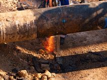 Worker staff cut big metal tube with grinder. Burning red parks Royalty Free Stock Image