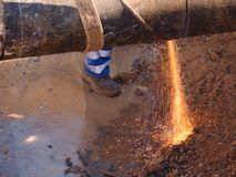 Worker staff cut big metal tube with grinder. Burning red parks. Worker staff is cutting big metal tube with hand grinder. Burning parks are flying down to wet Royalty Free Stock Image