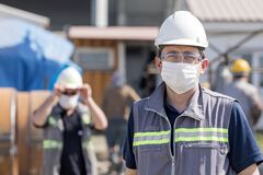 The worker staff, engineer protects himself from covid-19 coronavirus with a protective mask in the construction site.