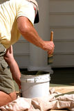 Worker Staining Deck. Rear view of man on knees brushing on deck stain royalty free stock photos