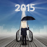 Worker on the stair with numbers 2015. Anonymous manager with a carton head and umbrella standing on the stair to the success door with numbers 2015 Stock Images