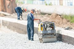Worker stamps filling brick by road roller. Tyumen, Russia - July 31, 2013: JSC Mostostroy-11. Bridge construction for outcome of Melnikayte street and Stock Photos