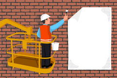 Worker standing in an assembly cradle glues a paper banner Stock Image