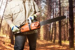 Worker standing with chainsaw in forest. royalty free stock image