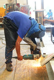 Worker standing grinding Royalty Free Stock Photos