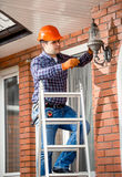 Worker standing on high ladder and changing bulb at outdoor lamp Stock Photos