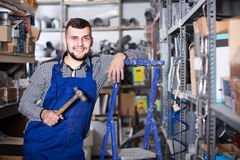 Worker standing in his workshop. Young worker with a tool in his hands is standing in his workshop Royalty Free Stock Images