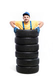 Worker is standing inside a pile of tires. Tyre service, worker is standing inside a pile of tires, white background, repairman, wheel mounting Royalty Free Stock Photos