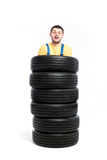 Worker is standing inside a pile of tires. Tyre service, worker is standing inside a pile of tires, white background, repairman, wheel mounting Stock Photo