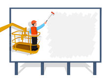 Worker standing on a ladder glues a paper banner. Stock Photos