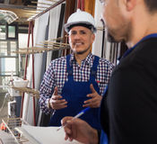 Worker standing near lathe, boss nearby. Positive worker standing near lathe, his boss with papers nearby stock photography