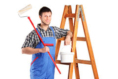 Worker standing next to a ladder. A manual worker standing next to a wooden ladder and holding a paint roller and bucket isolated on white background Royalty Free Stock Photography