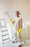 Worker standing with painting roller. Young man - worker standing with painting roller Stock Photo