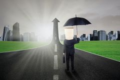 Worker standing on the upward road. Anonymous businessperson with a carton head and umbrella standing on the upward road Royalty Free Stock Photo