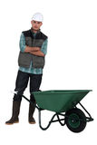 Worker standing by a wheelbarrow. Royalty Free Stock Images