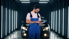 Repairman writes on a clipboard on a car background. Worker stands in a garage, holding a clipboard and writing. stock video