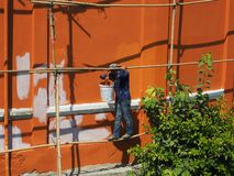 A worker stands on a makeshift scaffolding stock image