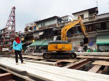 A worker stands near an excavator Royalty Free Stock Images