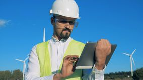 Worker stands near white wind turbines, typing on a tablet. Windmills, green energy concept. stock video