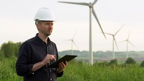 Worker stands near white wind turbines, typing on a tablet. Windmills, green energy concept stock video footage