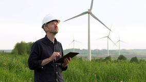 Worker stands near white wind turbines, typing on a tablet. Windmills, green energy concept. stock footage