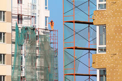 Worker stands on scaffolding of high-rise building Royalty Free Stock Image