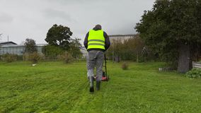 Worker starting cut the grass in rainy day stock video footage