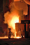Worker in a steel making factory. Taking sample from oven stock photography