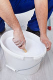 Worker stirring the paint - closeup on hands Royalty Free Stock Photo